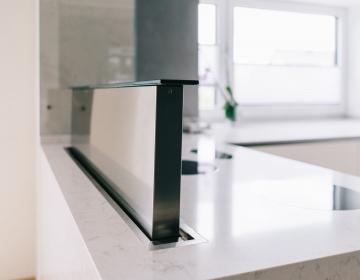Avar köök Sirius tööpinnast tõusva õhupuhasti ja I-Cooking induktsioonidega.